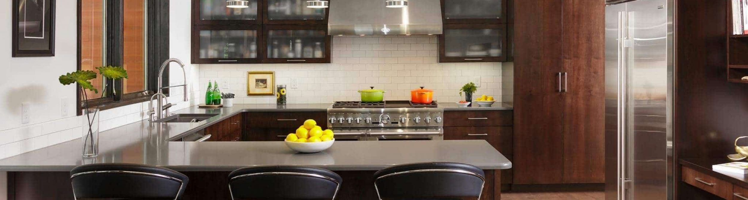 Dark colored kitchen cabinets with with stainless steel appliances