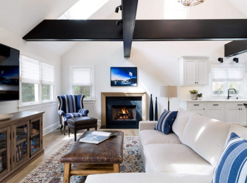 Living room to the side of a white colored kitchen